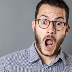 Bearded man with glasses reacts with shock